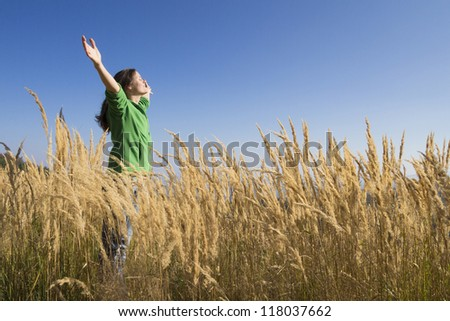 Happy young girl raising her arms with bliss and joy in the tall grass on a beautiful sunny day