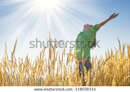 Happy young girl raising her arms with bliss and joy in the tall grass on a beautiful sunny day - stock photo