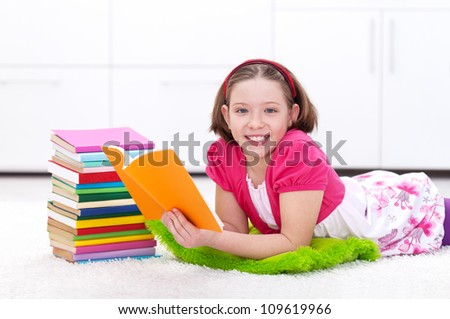 Happy young girl reading a book - back to learning and school