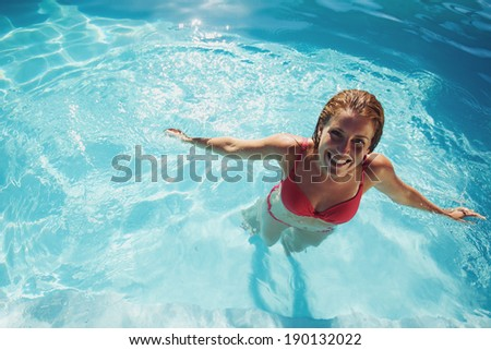 Happy young girl relaxing in a swimming pool. Smiling young woman wearing swimwear standing in pool looking at camera. - stock photo