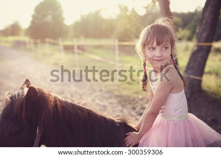 happy young girl riding horse - stock photo