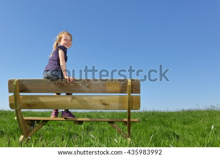 Happy young girl sitting on a bench in summer - stock photo