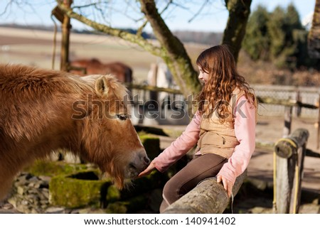 Happy young girl sitting on the paddock fence petting her horse - stock photo