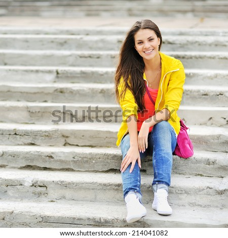 Happy young girl sitting on the stairs and smiling - stock photo