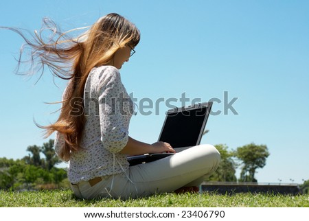 Happy young girl smiling and working on a laptop outdoors - stock photo
