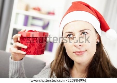 happy young girl want to guess christmas gift and looks a bit confused - stock photo