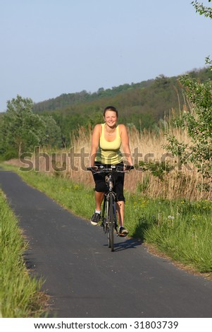 Happy young girl with a bike in front of the camera