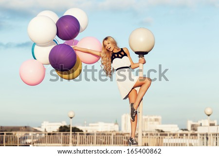 Happy young girl with big colorful latex balloons. Beauty Romantic Girl Outdoors. Woman  with long blond wavy hair  having fun on a lamppost on the background of blue sky. - stock photo