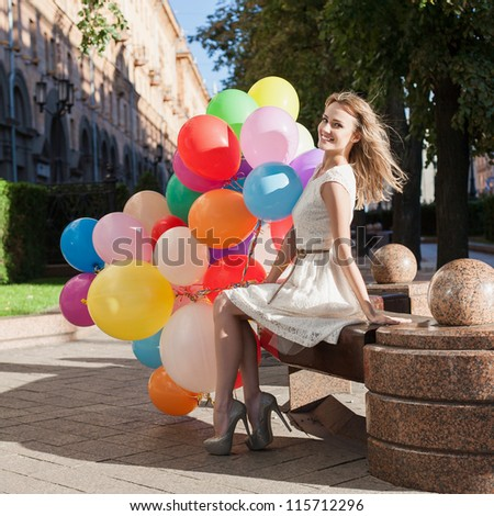 Happy young girl with colorful latex balloons keeping her hands, urban scene, outdoors - stock photo