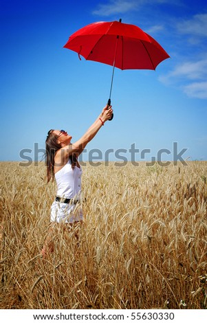 Happy young girl with red umbrella in the field - stock photo