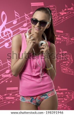 happy young girl with sexy pink style and sunglasses listening music with headphone and smiling  - stock photo