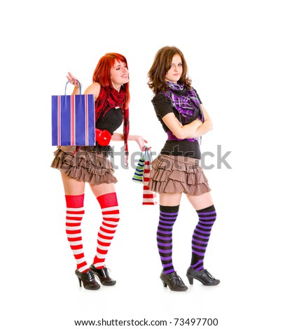 Happy young girl with shopping bags standing behind her dissatisfied girlfriend isolated on white - stock photo