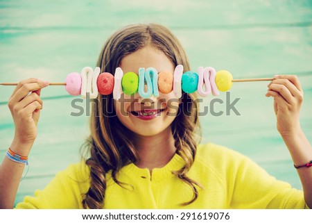 Happy young girl with sweets - stock photo