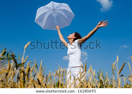 Happy young girl with umbrella in the field - stock photo