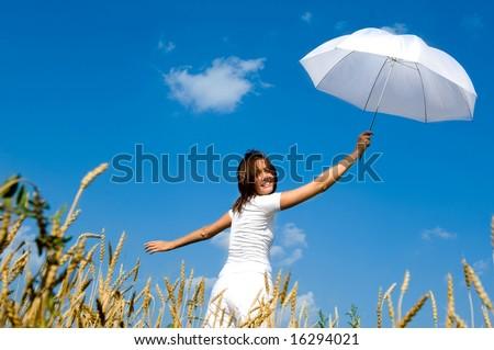 Happy young girl with umbrella in the field. Smiling face - stock photo