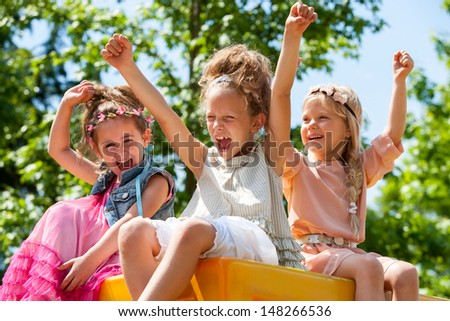 happy young girls raising hands together in park. - stock photo