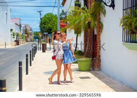 happy young girls, tourists walking on streets in city tour, Santo Domingo - stock photo