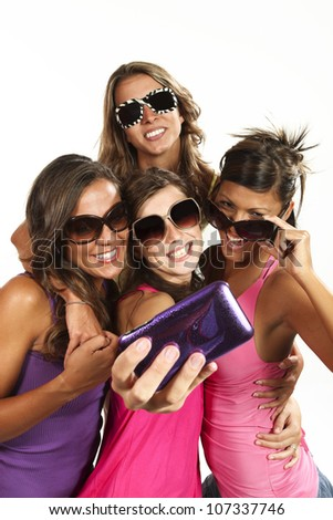 Happy young girls while taking pictures of themselves through cell phone - stock photo