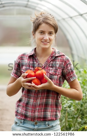 Happy young gorl with tomato harvest in hothouse - stock photo