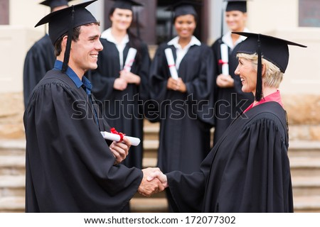 happy young graduate shaking hand with professor - stock photo