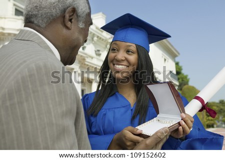 Happy young graduate student receiving gift from her father - stock photo
