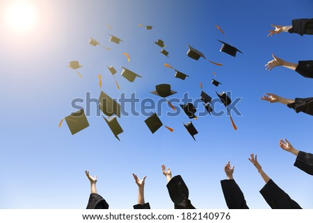 happy young graduates throwing hats - stock photo