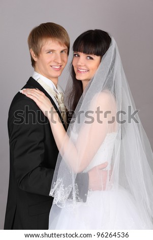 Happy young groom and bride embrace in studio on gray background - stock photo