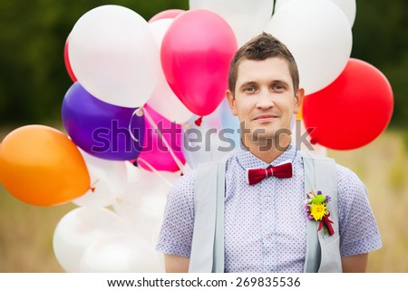 Happy young groom holding in hands colorful latex balloons outdoors. Handsome man having fun in wedding day. Smiling person. Carefree people. Decor for party celebration - stock photo