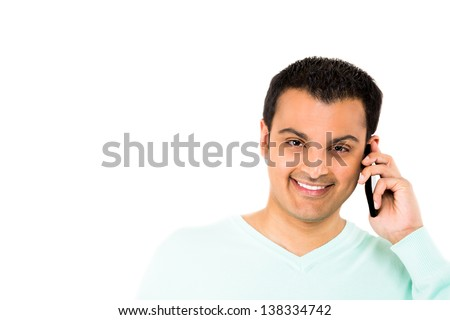Happy young guy talking on cell phone with copy space to left, isolated on white background - stock photo