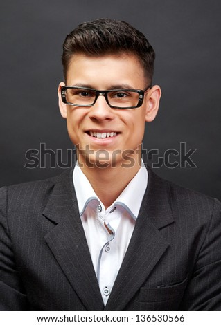 Happy young handsome businessman in suit over black background