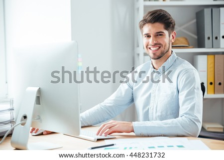 Happy young handsome businessman using laptop computer in office and looking at camera - stock photo