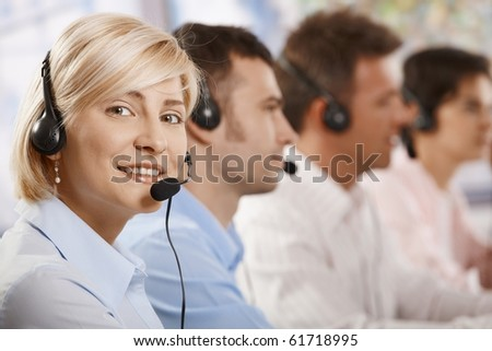 Happy young helpdesk operators receicving calls on headset, looking at camera, smiling.? - stock photo