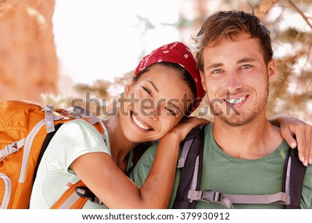 Happy young hikers backpacking on summer travel. Portrait of two friends teenagers or student couple wearing rucksacks bags smiling hiking during road trip vacation or doing volunteering.