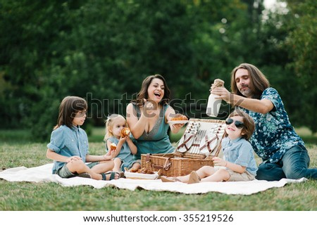 Happy young hipster family having fun, bowl, rising up, piggyback ride their children and relax for a picnic with basket full of milk and croissants in park on summer sunset  - stock photo