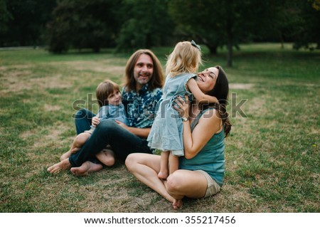 Happy young hipster family having fun, bowl,  rising up, piggyback ride their children in park on summer sunset  - stock photo