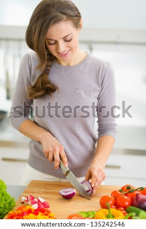 Happy young housewife cutting onion in modern kitchen
