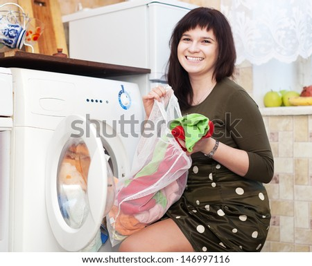 Happy young housewife doing laundry at her home