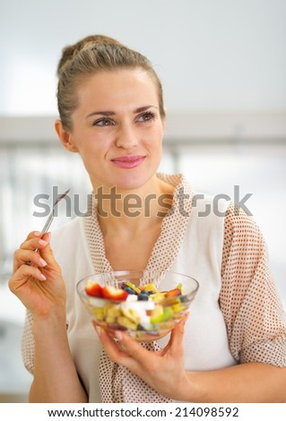 Happy young housewife eating fresh fruit salad