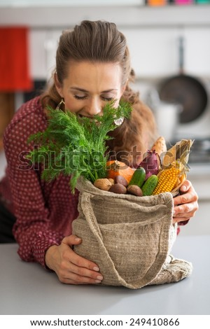 Happy young housewife enjoying freshness of vegetables from local market - stock photo