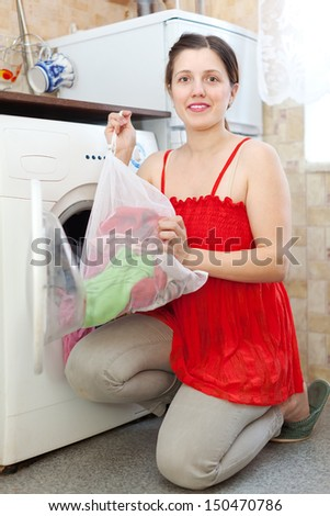 Happy young housewife in red doing laundry at her home