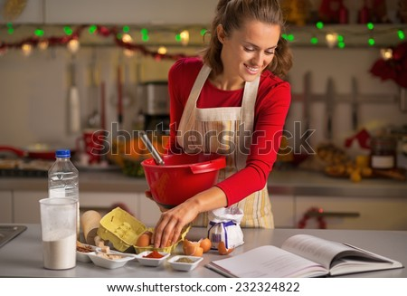 Happy young housewife making christmas cookies in kitchen - stock photo