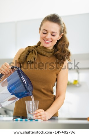 Happy young housewife pouring water into glass from water filter pitcher
