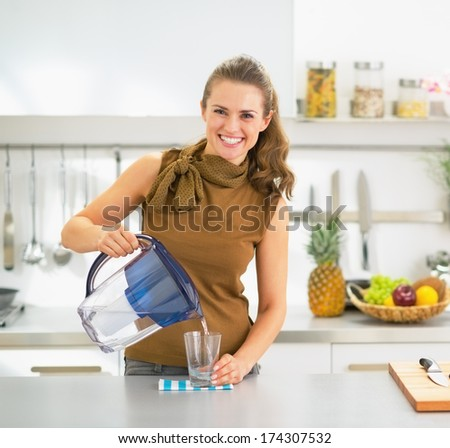 Happy young housewife pouring water into glass from water filter pitcher - stock photo