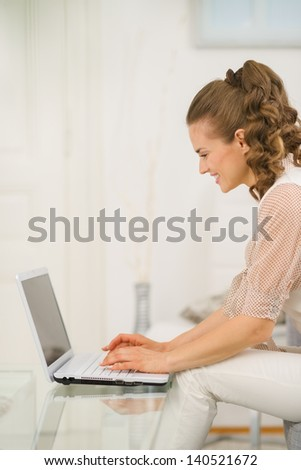 Happy young housewife sitting on divan in living room and using laptop