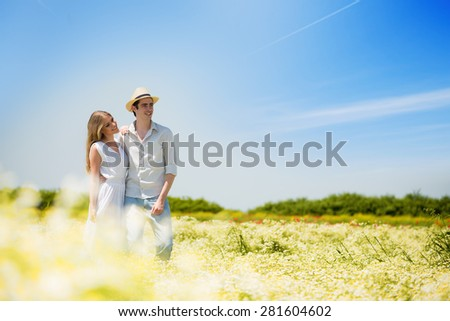 Happy, young hugging couple standing in a chamomile , daisy field, looking away.Copy space - stock photo