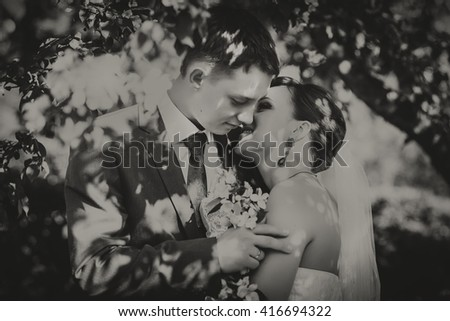 Happy young husband and wife, in the flowers, they look at the bouquet. Black and white photography.