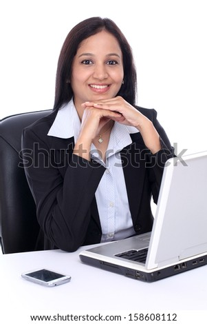 Happy young Indian business woman against white background - stock photo