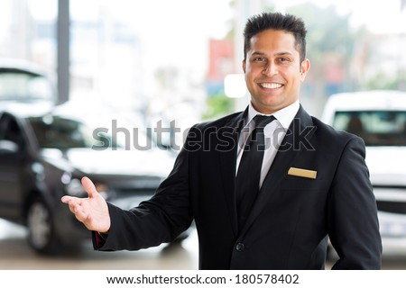 happy young indian car dealer standing inside showroom - stock photo
