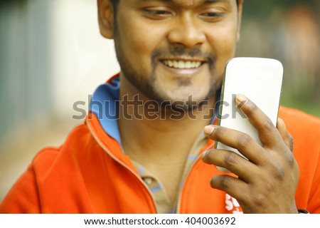happy young indian man smiling as he looks on at his smartphone using internet with broadband wifi and 4g connected - concept of asian people making use of technology to communicate with family - stock photo
