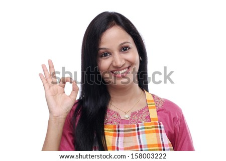 Happy young Indian woman wearing kitchen apron and showing thumbs up - stock photo